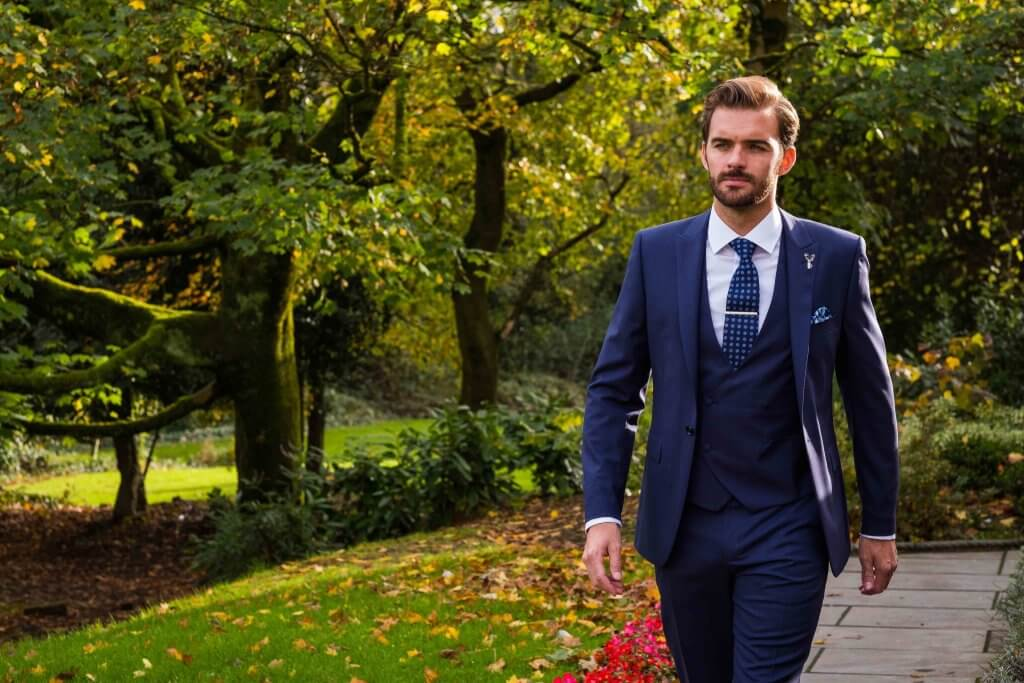 Gent walking through a park wearing a 3-piece blue check lounge suit