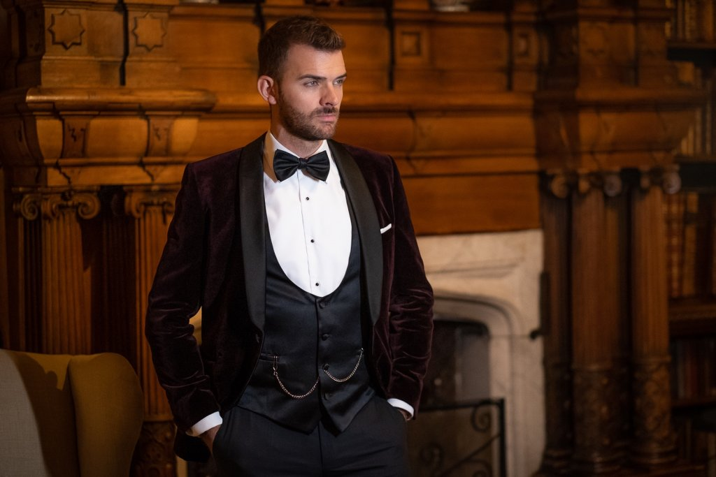 Gent stood by fireplace wearing a Burgundy velvet dinner jacket
