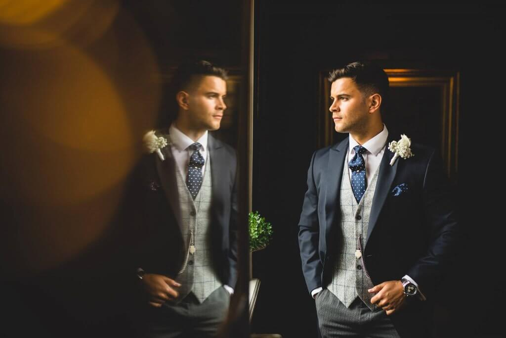 Groom looking into the distance wearing a navy morning suit, tweed waistcoat and striped trousers