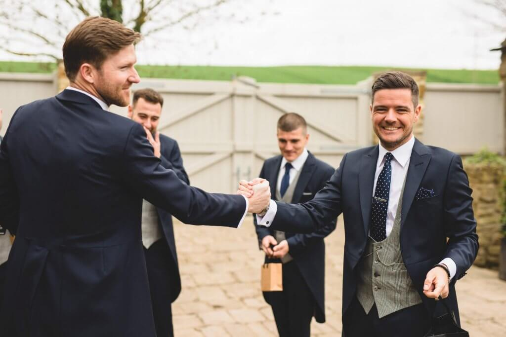 Groom and groomsmen wearing navy morning suits