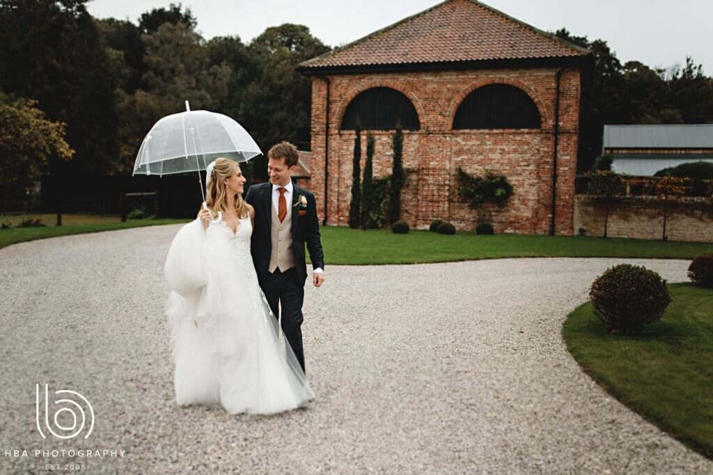 Bride holding an umbrella as she walks along gravel with the groom