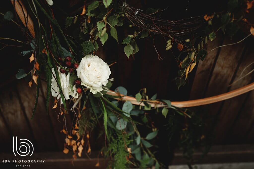 A floral arrangements with winter berries, white roses and green leaves