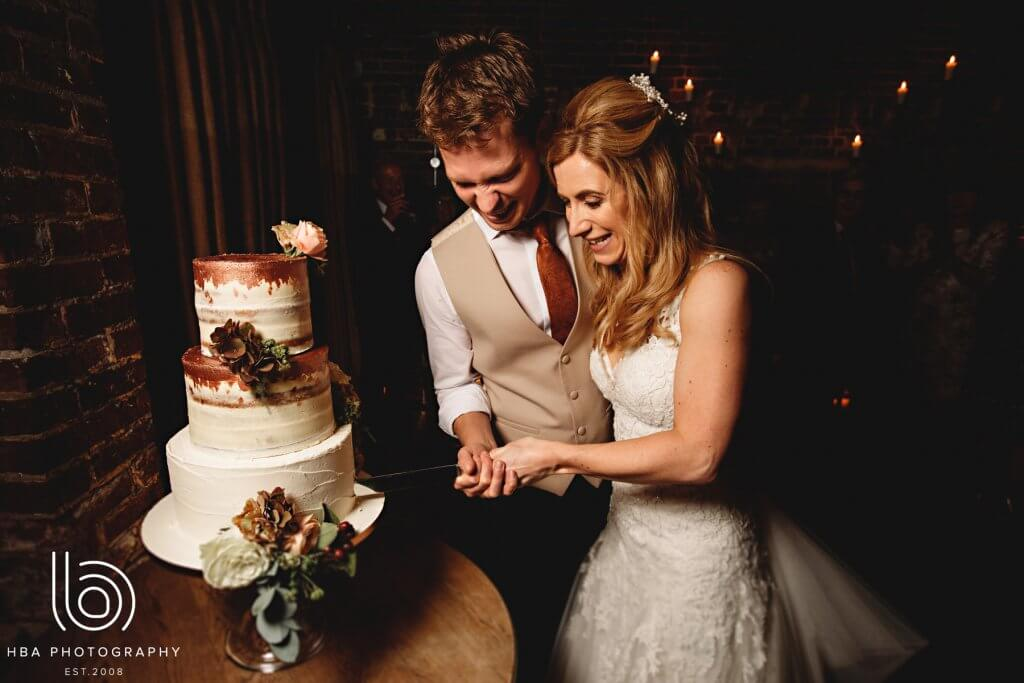 Bride and groom smiling as they cut into their wedding cake