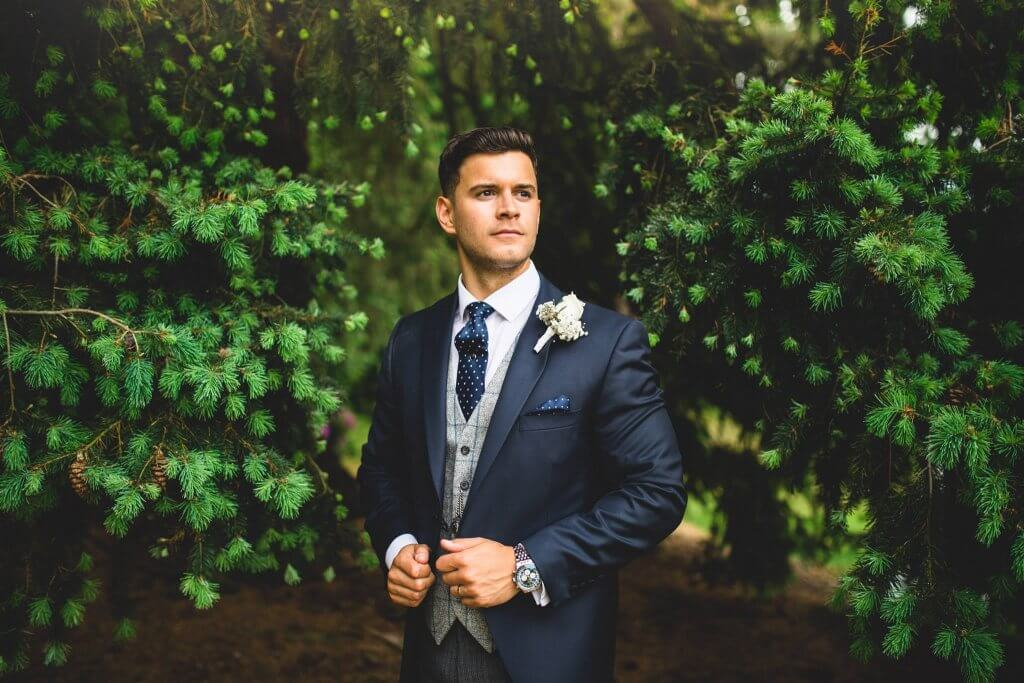 Groom stood by the trees wearing a navy morning suit